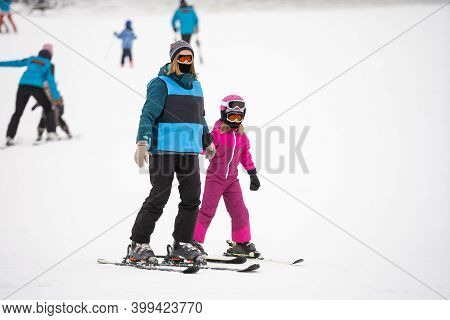 Professional Ski Instructor Is Teaching A Child To Ski On A Day On A Mountain Slope Resort With Snow
