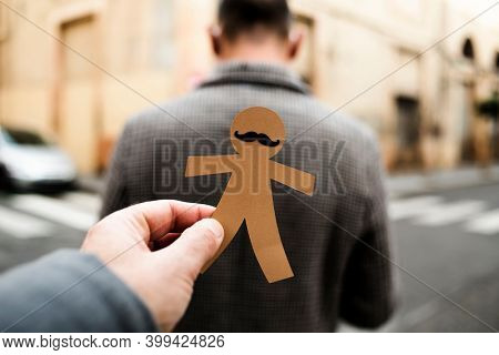 a man is about to attach a paper man doll to the back of another man, as a prank for dia de los inocentes, the innocents day, a feast held in spain and hispanic america equivalent to april fools day
