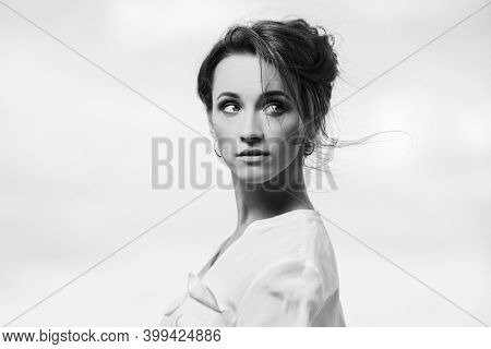 Young fashion woman in white shirt with bun updo hairstyle