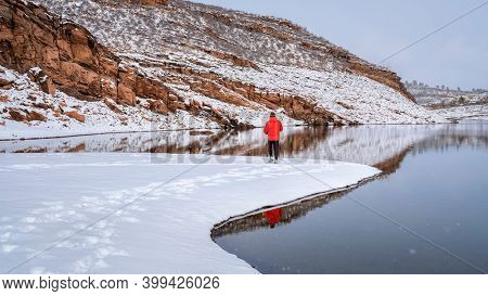 warmly dressed man is walking or jogging in winter scenery on a shore of mountain lake, Horsetooth Reservoir in Lory State Park, Colorado