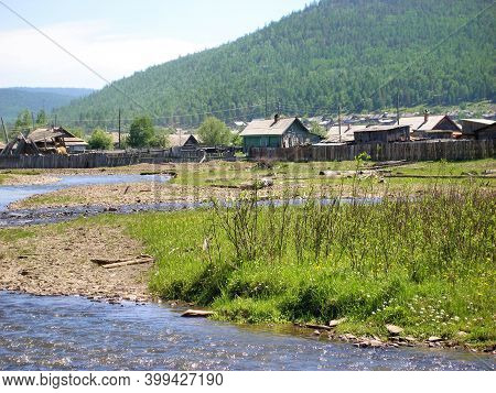 Siberian Village Dilapidated Houses And Fences, River Channel And Green Hills