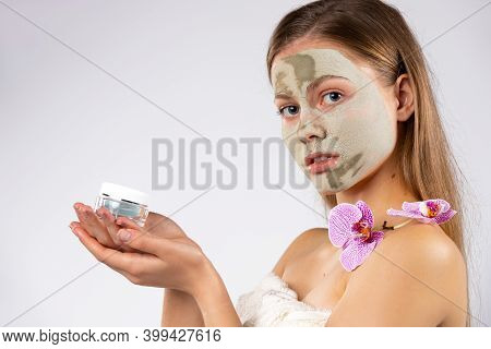Beauty Portrait. Girl With A Face Mask, Twig Of Orchid And Antiage Serum In Her Hands. White Backgro