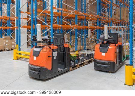 Two Order Picker Trucks In Distribution Warehouse