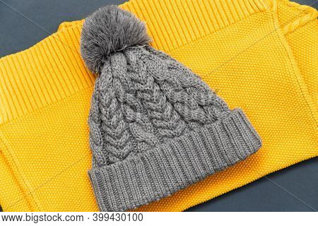 Knitted Yellow Sweater And Knitted Gray Hat On It In Trendy Colors On A Grey Background. Colors Of T