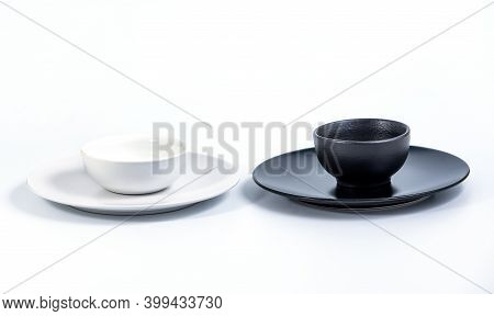 White And Black Bowls In White And Black Plates Isolated On White Background, Side View.