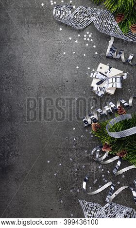Top View. Christmas Tinsel, Serpentine, Silver Ribbon And Christmas Gifts On Dark Background