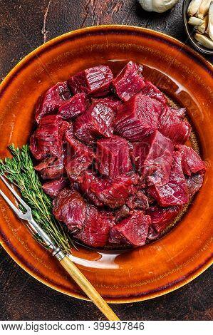 Raw Diced Deer Steak For A Venison Goulash. Dark Background. Top View