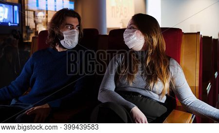 Young Couple In Masks Sitting In Movie. Media. Watching Masked Movie With Loved One During Pandemic.