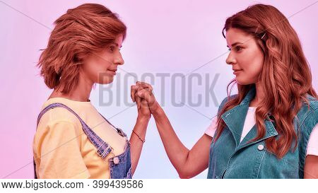 Portrait Of Two Attractive Young Girls, Twin Sisters Looking At Each Other, Holding Each Other Hand,