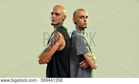 Portrait Of Two Young Men, Twin Brothers With Tattoos And Piercings Looking At Camera, Posing Togeth