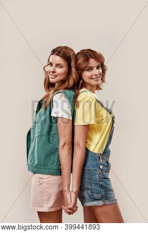 Portrait Of Two Attractive Young Girls, Twin Sisters In Casual Wear Smiling At Camera, Holding Hands