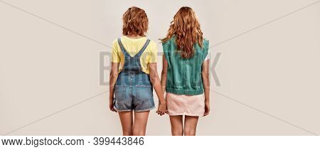 Back View Of Two Young Girls, Twin Sisters In Casual Wear Holding Hands, Posing Together, Standing I