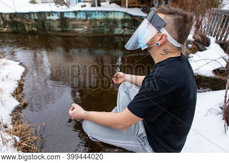 Side View Of A Man In A T-shirt Sitting In The Yoga Lotus Flower Position On The Edge O Fa Lake In T