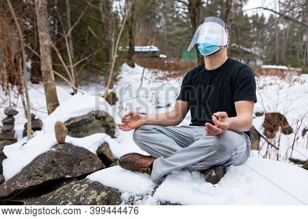 Funny Shot Of A Young Man In A T-shirt Sitting In The Yoga Lotus Flower Position On A Big Rock In Th