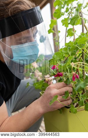 Close Up, Side View Of A Man Trying To Smell A Flower Through Several Layers Of Safety Covid Protect