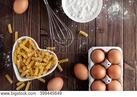Raw pasta fusilli with eggs on wooden background. Top view of Italian cuisine ingredient.