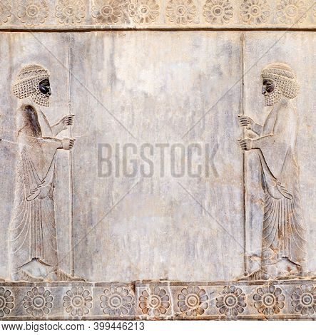 Ancient wall with bas-relief - two assyrian warriors with spears, Persepolis, Iran. Square background with embossed image persian bearded mans. Mock up template. Copy space for text