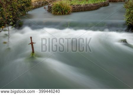 Long Exposure Of A Waterfall Flowing Past The Sword In The Stone In Cheddar Village In Somerset