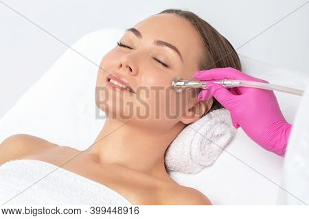 The Cosmetologist Makes The Procedure Microdermabrasion Of The Face Skin Of A Beautiful Girl In A Be