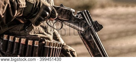 Hunter Man. Hunting Period. Male With A Gun, Rifle. Man Is Charging A Hunting Rifle. Male Hunter In