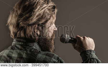 Man With A Beard Holding A Microphone And Singing. Bearded Man In Karaoke Sings A Song Into A Microp