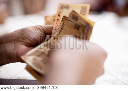 Indian Man Holding And Counting Indian Rupee Notes For Payment To Home House Help And Maids Showing