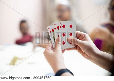 Woman Holding Cards With Out Of Focus Family Members In The Distance Showing A Family Playing Cards
