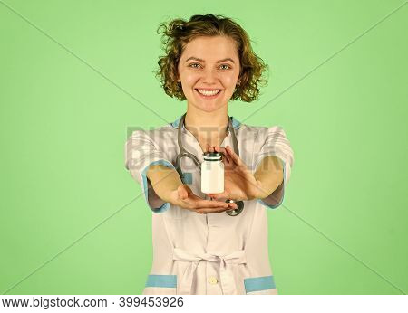 Confident Doctor Holding A Pill Bottle. Useful Medication. Doctor Offering To Drug Tablet. Introduci