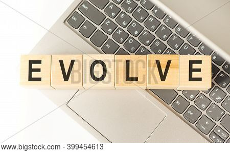 Word Evolve. Wooden Cubes With Letters Isolated On A Laptop Keyboard. Business Concept Image.