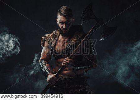 Portrait Of Evil Nordic Pagan In Light Armour With Fur Staring At Camera And Holding Two Handed Axe