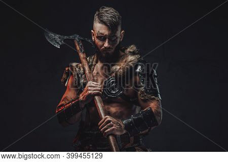 Dressed In Light Armour With Fur Scandinavian Seafarer Armed With Two Handed Axe Poses In Dark Backg
