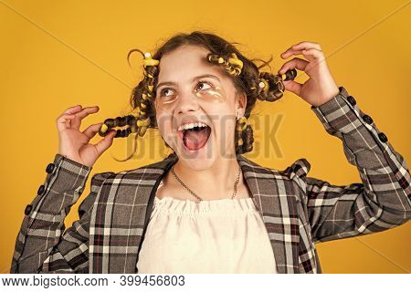 Girl With Curlers And Hair Clips In Her Hair On Yellow Background. Little Girl Curlers Around Her Ha