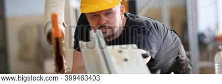 Serious Young Man In Yellow Helmet Working In Manufactured Joinery Workshop