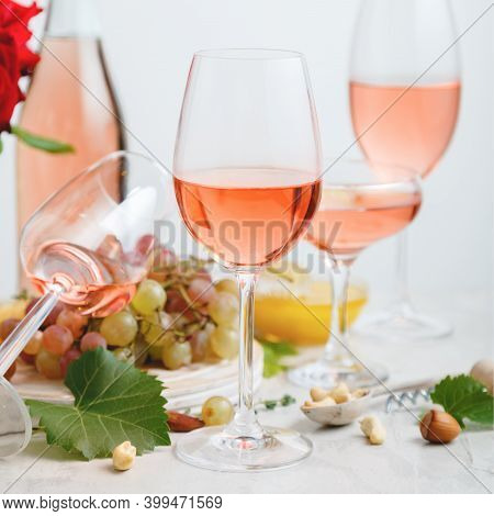 Rose Wine In Different Types Of Glasses On Light Concrete Background With Grapes. Wine Composition W