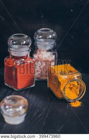 A Set Of Spices In Small Jars With Cork Lids. Pink Salt, Ginger, Turmeric, Masala, Paprika, Smoked P