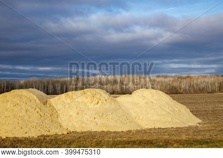 Piles Of Agricultural Lime (crushed Limestone) Ready To Be Spread On The Field To Neutralize Soil Ac