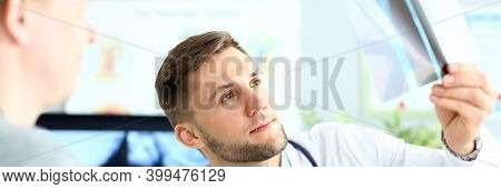 Male Radiologist In White Lab Coat Analyzing Radiography Results While Having Meeting With Patient