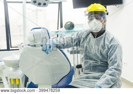 Portrait Of A Peruvian Young Dentist With A Mask And Visor In A Dental Office. Covid - 19 Virus Prot