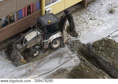 An Excavator Digs A Trench In Winter. The Excavator Is Working Next To A Residential Building. Excav