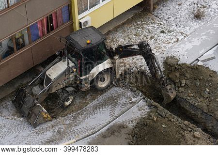 An Excavator Digs A Trench Next To A Residential Building. Excavator Bucket In A Trench. Excavator W