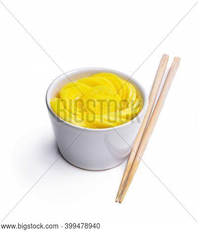 Marinated  Daikon Slice With Chopsticks Isolated On White