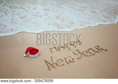 Happy New Year With Santa Red Hat Written On Sand By Hand On The Tropical Beach With Ocean. Christma