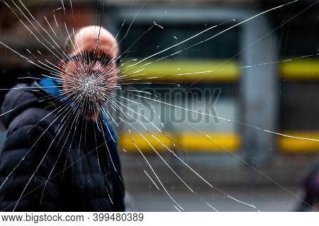 Kaunas, Lithuania - October 5, 2019: Broken Glass, Cracks On Glass Window.  A Passerby Behind The Wi