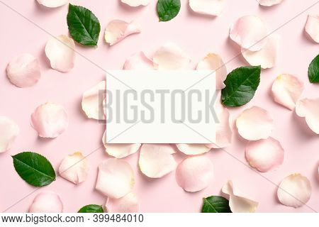 Blank Paper Card Mockup With Rose Petals And Green Leaves On Pink Background. Flat Lay, View From Ab