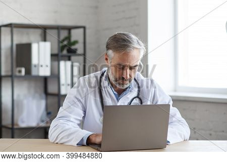 Portrait Of Senior Grey-haired Male Doctor In His Office Using Laptop For Video Chat With A Patient.
