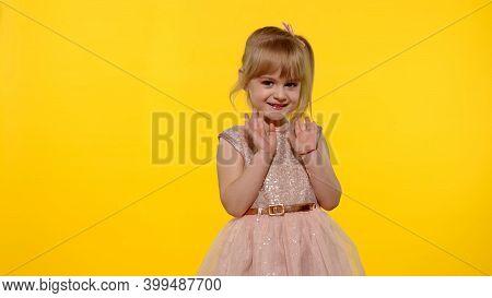 Hello Or Bye. Little Smiling Blonde Child Kid Girl 5-6 Years Old In Pink Dress Posing Waving Greetin