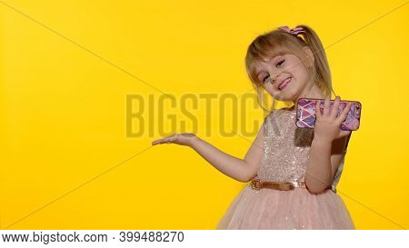 Child Girl Using And Holding Smartphone. Kid Pointing At Something With Hands, Showing A Product, Sm