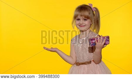 Kid Pointing At Something With Hands, Showing A Product, Smiling And Offering An Imaginary Object. C