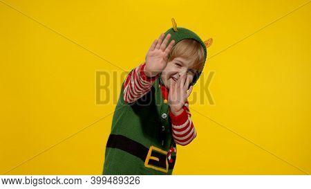 Scared Blonde Kid Teen Girl In Christmas Elf Santa Helper Costume Looking At Camera Afraid Cover Hid