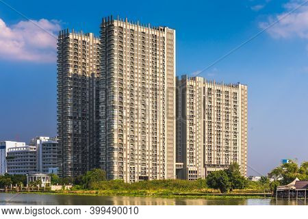 Modern Apartment Buildings On A Sunny Day With A Blue Sky On Chao Phraya River Embankment In Bangkok